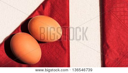 two orange eggs in a shell lie on a napkin of claret color, the composition on white material, lies the second napkin nearby dividing a picture into several parts