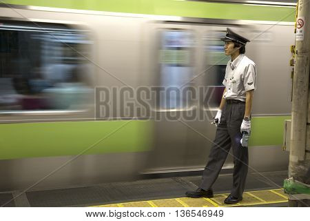 TOKYO-JAPAN, 27 June 2016:  Train controller at the JR train station and fast moving train. It is one of Tokyo's busiest and most important lines in Tokyo, Japan.