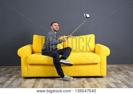 Young handsome man taking selfie on yellow sofa in the room