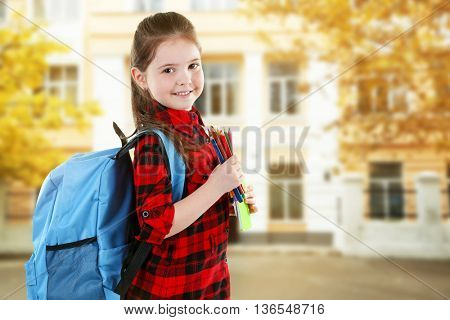 Little girl with blue back pack holding pencils on blurred school building background