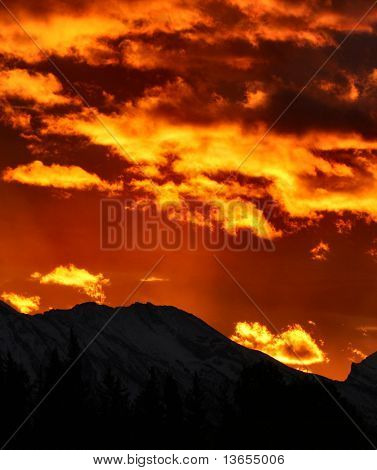 Incredible Mountain sunrise with dimly lit mountains in the foreground, full of colour