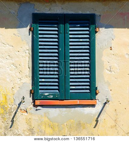 Closed window with green shutters of a house with plaster degraded