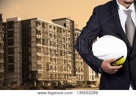 Engineer Holding White Helmet For Workers Security On Contruction Background