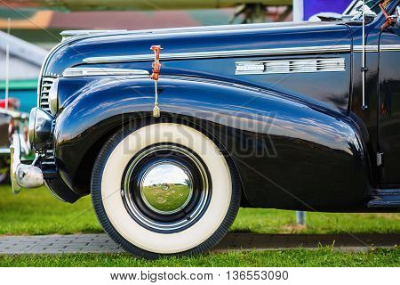 MINSK BELARUS - MAY 07 2016: Close-up photo of black Buick Eight 1940 model year. Vintage retro auto. Fender and the front wheel of the car. Side view. Selective focus.
