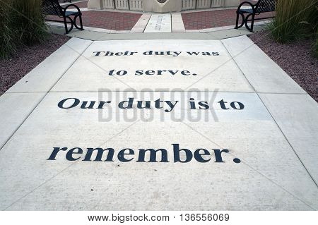SHOREWOOD, ILLINOIS / UNITED STATES - AUGUST 30, 2015: The sidewalk at the Village of Shorewood Towne Center Veterans' Memorial bears the motto