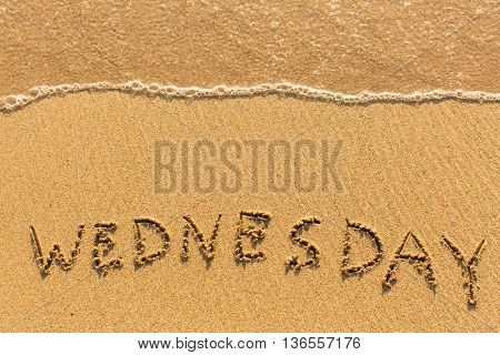 Wednesday - drawn by hand on a sandy golden sea beach.