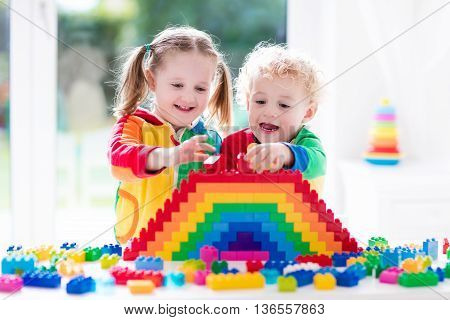 Child playing with colorful toys. Little girl and funny curly baby boy with educational toy blocks. Children play at day care or preschool. Mess in kids room. Toddlers build a tower in kindergarten.