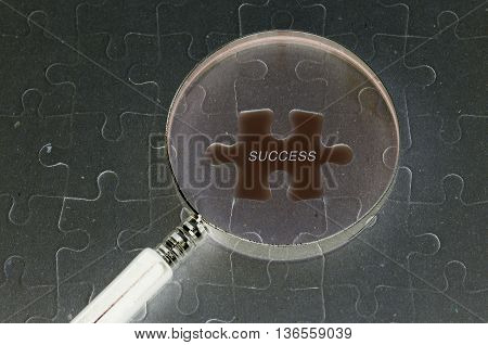 Business concept : Jigsaw puzzle background and magnifying glass and copyspace area with SUCCESS word