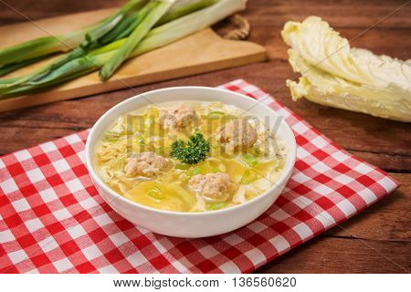 Bowl of wanton soup with fried fish balls on the table in restaurant
