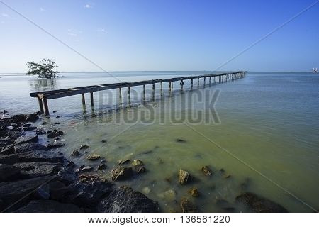 wooden pier in caribbean sea with beautiful blue sky and copy space area.