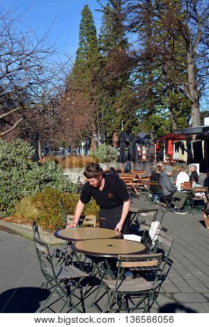 Hanmer Springs New Zealand - June 25 2016: Waiter cleans a table at popular outdoor cafe in the Tourist Town of Hanmer Springs North Canterbury.