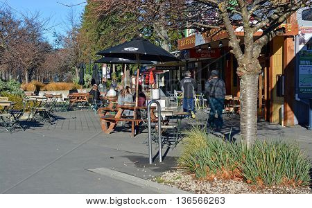 Hanmer Springs New Zealand - June 25 2016: People at a popular outdoor cafe in the main street of the Tourist Town of Hanmer Springs North Canterbury in winter.