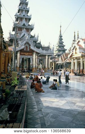 RANGOON / MYANMAR - CIRCA 1987: Buddhists sit and worship at the Shwedagon Pagoda in Rangoon.