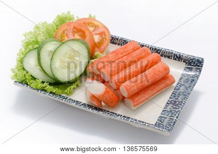 Crabmeat sticks with sliced cucumber and tomato on plate