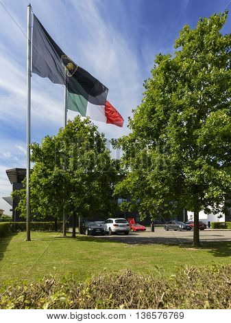 Sant'Agata Bolognese, Italy - April 30, 2016: Flags in front of the Lamborghini factory with the factory logo and the Italian flag in the day of the 100th Ferruccio Lamborghini Anniversary