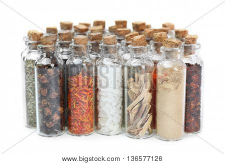 Assorted dry spices in glass bottles on white background