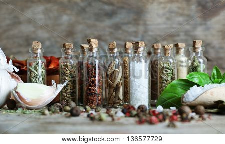Assorted dry spices in glass bottles on wooden background
