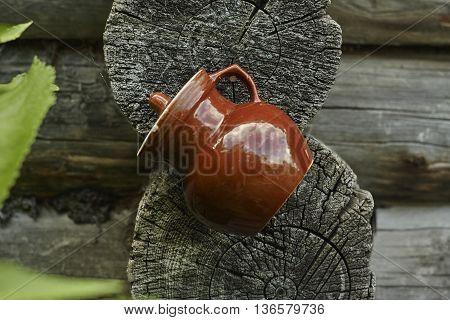 brown jug near old blockhouse wall close up