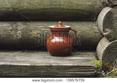 brown old jug near blockhouse wall close up