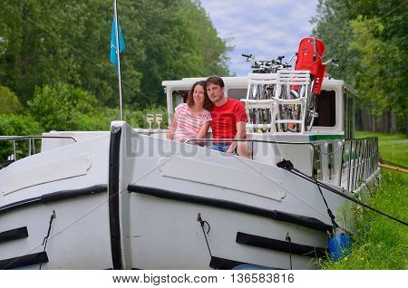 Romantic vacation, travel on barge boat in canal, happy couple having fun on river cruise in houseboat