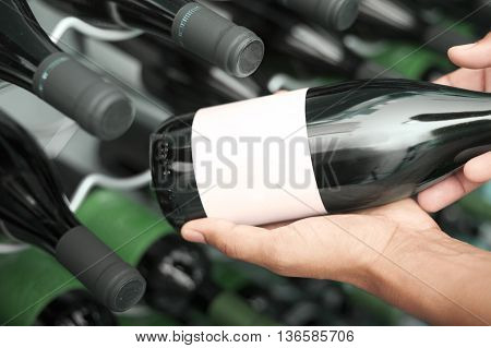 Wine taster showing wine bottles with copyspace