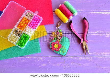 Homemade keychain felt embellished with beads. Colorful fabric heart keychain, woman's or children's key chain. Box with beads, pliers, felt sheets, needle, thread. Set for kids handicraft