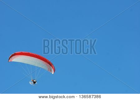 PUTRAJAYA, MALAYSIA - MARCH 20 : A Paragliding enthusiasts flying in blue sky during 3rd Putrajaya International Hot Air Balloon Fiesta March 20, 2011 in Putrajaya, Malaysia.