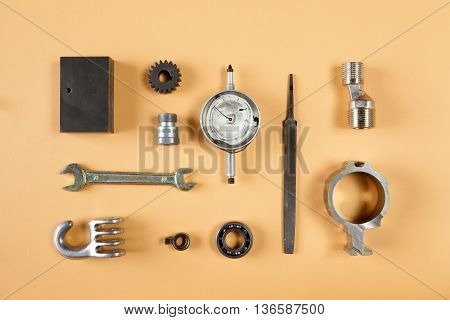 Mixture of different pieces of tools and machinery on orange background