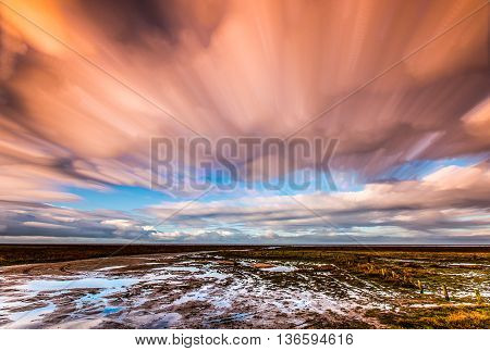 timelapse movement of clouds across marshland and water