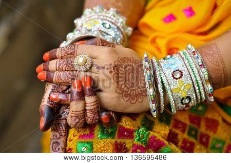 Close up photo of Indian woman's hand with henna tattoo and traditional bangles