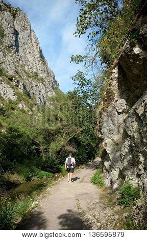 one hiker with backpack on path of Turda Gorge Natural Reserve, Romania
