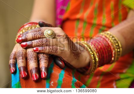 Close up photo of Indian woman's hand with henna tattoo and red bangles