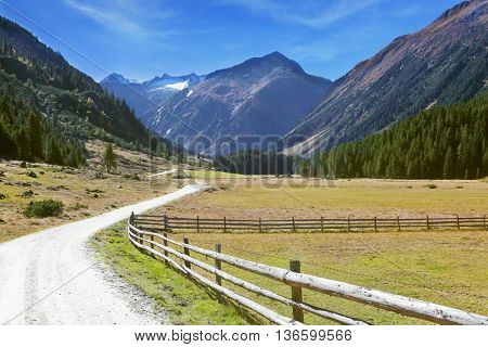 Rural idyll. Headwaters National Park Krimml. Farm fields separated from the dirt road the low fence made of logs.
