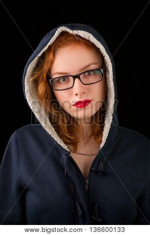 Red-haired girl with eyeglasses and bright red lipstick in blue hooded coat. On black background