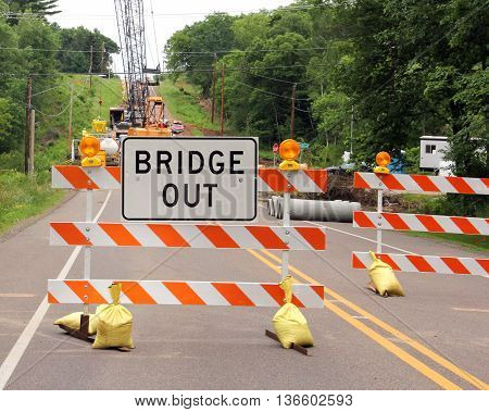 Road closed with a bridge out sign on a barricade
