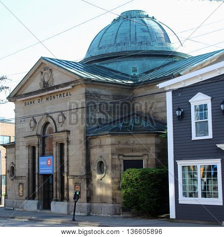 SYDNEY, NOVA SCOTIA CANADA - JULY 1: The Bank of Montreal building in Sydney Nova Scotia Canada is a 117-year-old landmark.  The bank is moving in July 2016 and the historic stone building has been donated to the Old Sydney Society to be converted into a
