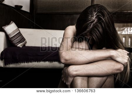 Sad woman sitting alone in a empty room next to the bed. domestic violence.