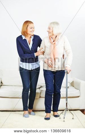 Caregiver from nursing service helping senior woman with cane at home