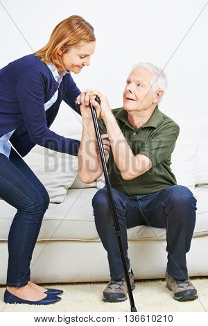 Woman helping senior man with cane getting up from sofa at home