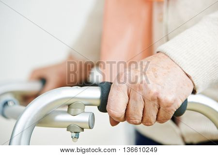 Hands of an old woman holding on to a walker