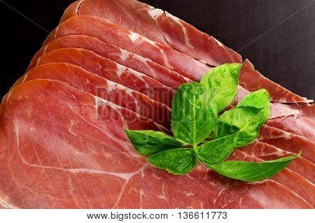Prosciutto. Smoked pork rashers with basil. Italian appetizer.