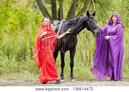 Two women in red and violet clothes with chestnut horse in park.