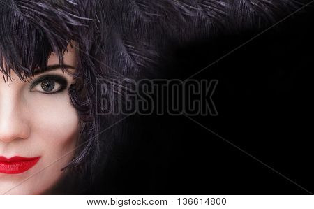 Close-up portrait of mysterious young beautiful woman with black feather headdress on black background with copy space. Model fashion shooting. Smoky eyes make-up. Red sensual lips. Perfect pure skin. Femme fatale. Retro style. Vintage style. Cabaret girl