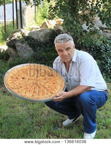 man hold platter with fresh baked baklava wih walnuts for ramadan holiday