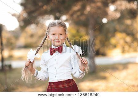Smiling pupil girl 6-7 year old posing outdoors wearing school uniform. First grade. Back to school.