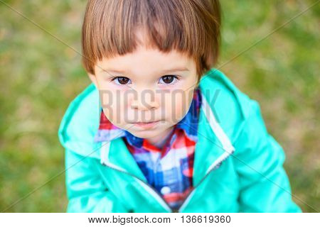 Cute Little Toddler Boy In A Park Looking At Camera