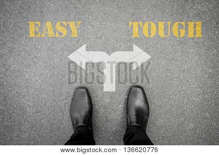 black shoes standing at the crossroad and have to make a decision between easy or tough