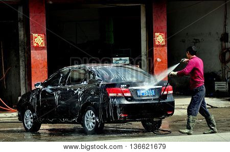 Long Feng China - March 5 2013: Worker at a local car wash shop hoses suds off a customer's automobile using a high-powered hose