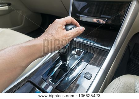 hand on automatic gear shift Man hand shifting an automatic car