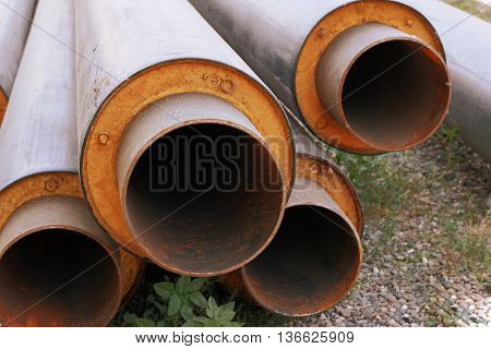 Steel water pipes with PVC isolation shell in stack on ground in construction site, view from end open holes
